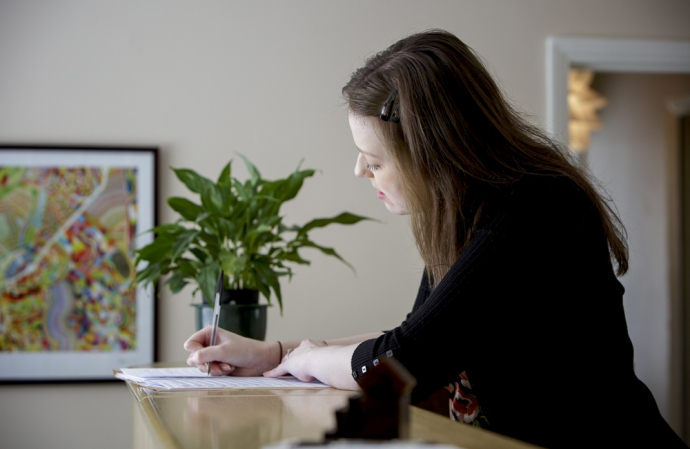 Our receptionist Eve fills out a new patient's details